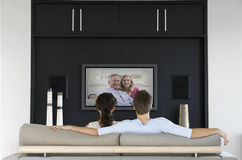 Back view of couple watching movie on television in living room Stock Photo