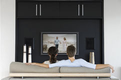 Back view of couple watching movie on television in living room Stock Photography