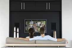Back view of couple watching movie on television in living room Stock Images