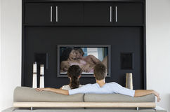 Back view of couple watching romantic movie on television in living room Stock Image
