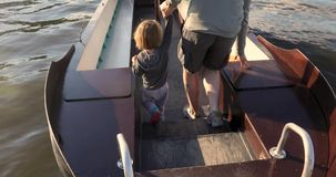 Man holding child by hand walking on boat stock footage