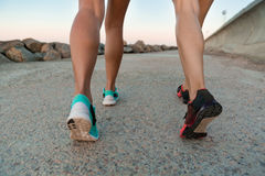 Back view cropped image of two young women in sneakers Royalty Free Stock Image