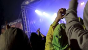 Back view of crowd of people at the concert. Footage. Silhouettes of concert crowd in front of bright stage lights. Back view of crowd of people at the concert Royalty Free Stock Photo