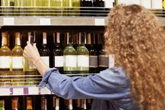 Back view of curly woman chooses wine on shelf in supermarket, prepares for holiday or special day, makes purchase. Wavy cute youn stock images