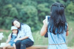 Back view of asian child girl is using tablet taking a photo royalty free stock photo