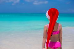 Back view of cute girl in red hat santa claus on. Little girl in red hat santa claus on the beach Royalty Free Stock Images
