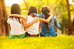 Back view of cute girls seated on green Royalty Free Stock Photos