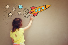 Back view of cute kid (girl) imagine space rocket with set of infographics over textured wall background.  Royalty Free Stock Photos