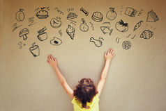 Back view of cute kid imagine various foods with set of infographics over textured wall background Royalty Free Stock Photos