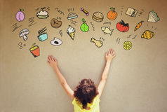 Back view of cute kid imagine various foods with set of infographics over textured wall background Stock Photo