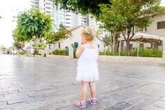 Back view cute little blondy toddler girl in white dress standing along on the alley in the city park. Childhood concept. Soft sel. Ective focus, copy space royalty free stock image