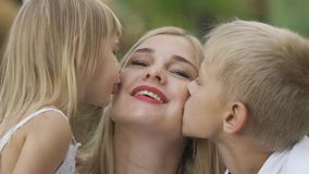 Back view of cute little girl and boy kissing cheek of mother. Woman laughing and hugging son and daughter. Happy family. In the park. One parent. Motherhood stock footage