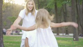 Back view of cute little girl running toward her mom. Woman laughing and hugging daughter. Happy family in park. One. Back view of cute little girl running stock video footage