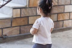 Back view of cute little girl walking at outdoors. Child on the playground outdoor background royalty free stock image