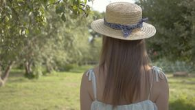 Back view of cute young woman in straw hat and long white dress walking through the green summer garden. Carefree rural. Attractive young woman in a straw hat stock video footage
