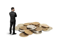 Back view cutout businessman standing in front of a copper heap ruble coins Stock Photography