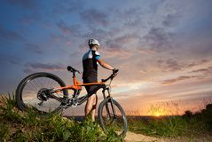 Back view cyclist male in helmet and sports clothes rests on the background of sunset. Back view of cyclist male in a helmet and sports clothes rests on the Stock Photography