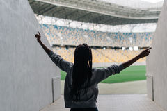 Back view of the dancing afro-american teenager going to the sport stadium. Royalty Free Stock Images