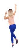 Back view of dancing young beautiful  woman. girl  watching. Royalty Free Stock Photo
