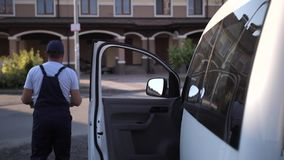Employee of delivery service carrying pizza boxes. Back view of delivery man in cap and overalls taking two pizza boxes out from van and carrying order to client stock footage