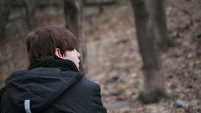 Back view of depressed young man sitting alone outdoors, having sad thoughts stock video