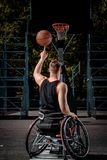 Back view of a disabled basketball player in wheelchair spinning basketball on his finger on open gaming ground. Back view of a disabled basketball player in a Royalty Free Stock Images
