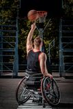 Back view of a disabled basketball player in wheelchair spinning basketball on his finger on open gaming ground. Back view of a disabled basketball player in a Royalty Free Stock Photography