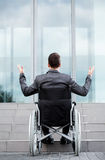 Back view of a disabled man in front of stairs stock photo