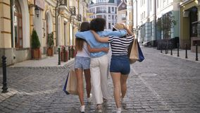 Back view of diverse fashion girls shopping. Back view of diverse multiethnic fashion women walking on city street holding shopping bags. Group of three stock video
