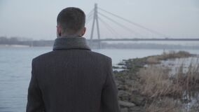 Back view of elegant Caucasian man standing on riverbank and looking at city bridge at the background. Lonely brunette
