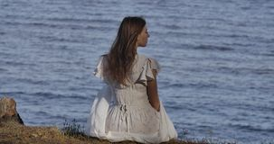 Back view of an elegant Caucasian woman in light white dress sitting on the beach and thinking. Beautiful girl resting stock video