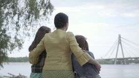 Back view of elegant mature woman sitting on the grass on riverbank, hugging two cute granddaughters, talking to them. Back view of an elegant mature woman stock video footage
