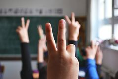 Classroom students hands raised stock images