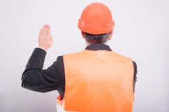 Back view of engineer wearing hardhat making oath gesture Royalty Free Stock Images