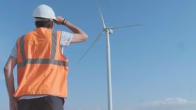 Back view of engineers discussing against turbines on wind farm while walking along road on sunny day.  stock footage