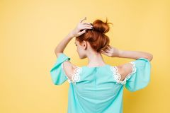 Back view of Enigmatic ginger woman in dress posing. Over yellow background Royalty Free Stock Photography