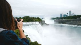 Back view of excited journalist woman with camera taking photo of epic Niagara Falls, looking around smiling slow motion. Happy professional photographer takes stock video footage