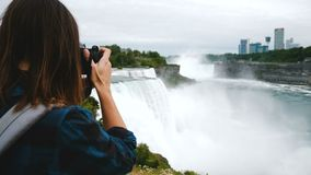 Back view of excited tourist woman with backpack and camera taking a photo of epic Niagara Falls view slow motion. Back view of excited tourist woman with stock video