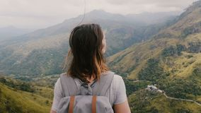 Back view excited tourist woman with backpack, hair blowing in the wind meditating, watching epic mountains view scenery. Back view excited tourist woman with stock video footage