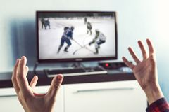 Back view of excitement man with gesturing hands. Up how watching ice hockey in television at home. Rear view of male Watching sport in TV. an excited fan is Royalty Free Stock Photography