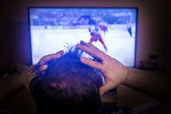 Rear view of male head Watching sport in TV. Back view of excitement man with gesturing hands up how watching ice hockey in television at home. Rear view of Stock Photos