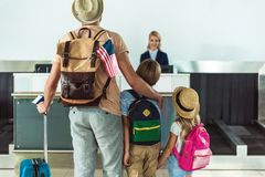 Family going to check in desk. Back view of family with backpacks going to check in desk at airport Stock Photo