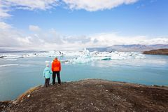 Family in iceland. Back view of family, father and son, enjoying beautiful view at iceberg lagoon in jokulsarlon national park in iceland, copy space on right royalty free stock photography