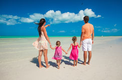 Back view family of four on caribbean beach Stock Image