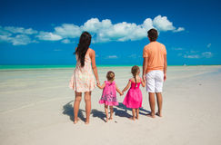 Back view family of four on caribbean beach Royalty Free Stock Image