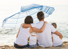 Back view on family of four sitting on beach Stock Photography