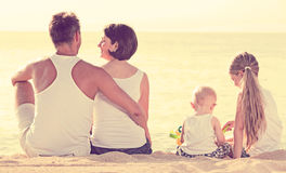 Back view on family of four sitting on beach Royalty Free Stock Photography