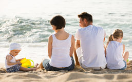 Back view on family of four sitting on beach Royalty Free Stock Photo