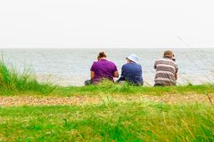 Back view of a family sitting on Minsmere beach in the UK royalty free stock photo
