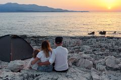 Back view of family, sitting on rock beach, admiring setting sun over sea. Back view of happy young family, sitting on rock beach near tent and admiring setting stock images